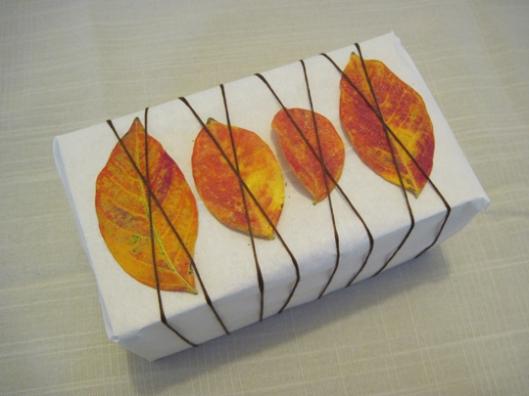 Si quieres ir con un estilo moderno, usa cuerda y hojas de colores para adornar tu regalo.