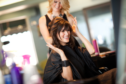 109721602-happy-young-woman-getting-hair-styled-as-gettyimages