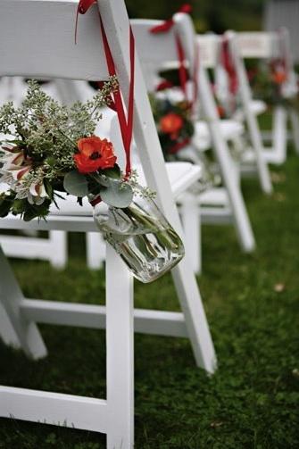 Colgar envases de cristal con cinta en las sillas de jardín es también una manera económica y simple de decorar tu camino hacia el altar.