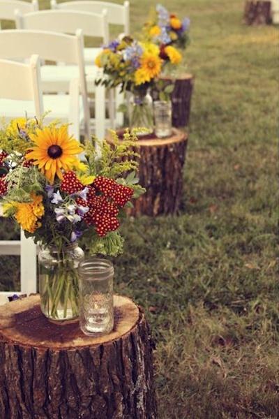 Unos simples troncos con flores y envases reusados pueden ser el toque perfecto para boda en el exterior.