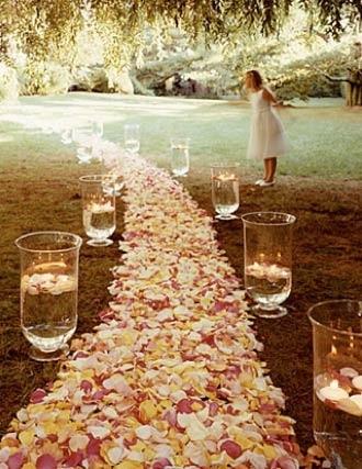 Crear una vereda de flores y solo colocar velas con agua es sencillamente espectacular, especialmente en bodas que sucederán entrada la tarde.