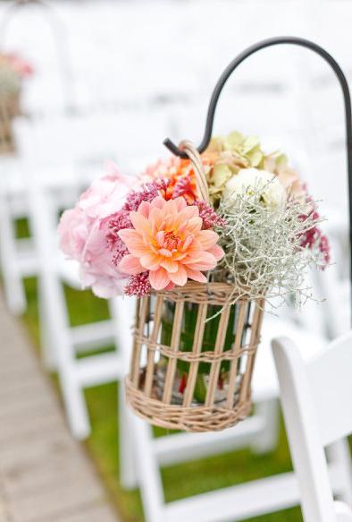Colocar ganchos en la tierra y colgar envases o canastas como esta es también una buena opción para este tipo de boda.