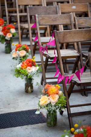 Puedes colocar bases altas, medianas o bajas al lado de cada hilera de sillas. Si tu boda es menos formal, puedes considerar usar banderines como en esta imagen.